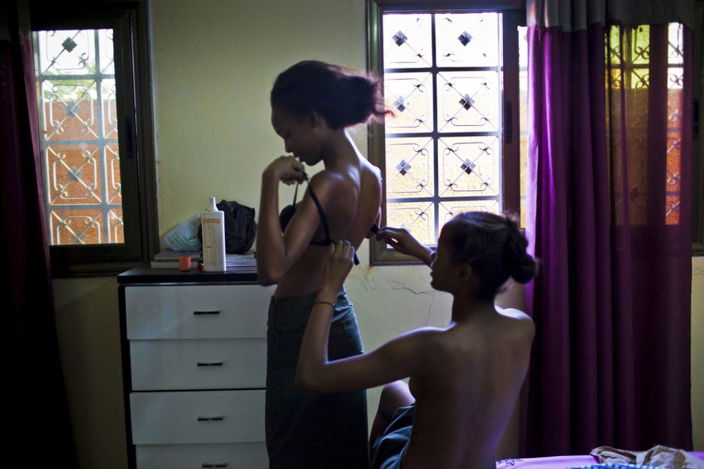 Nadia, 15, helps her older sister Miriam, 17, to put her bra.