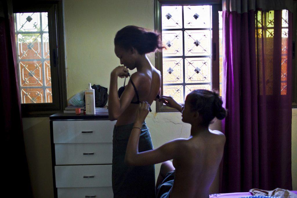 Nadia, 15, helps her older sister Miriam, 17, to put her bra.